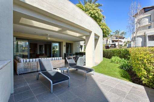 Die überdachte Terrasse bietet Liegen an